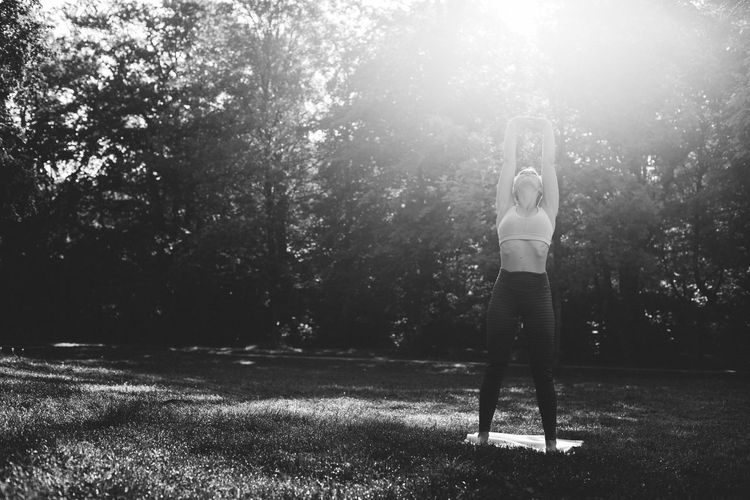 Full length of woman standing on field doing yoga