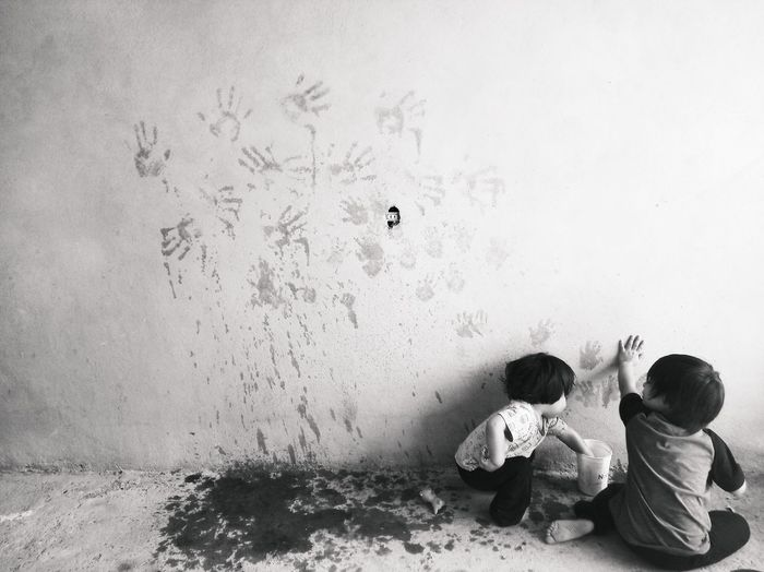 Boys painting wall with hand prints