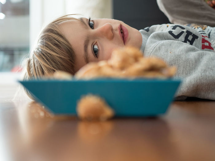 Boy lying by cereal bowl on floor at home
