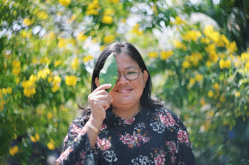 Portrait of smiling woman standing on yellow flowering plants