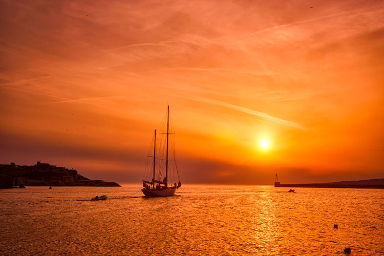 Silhouette sailboat on sea against romantic sky at sunset