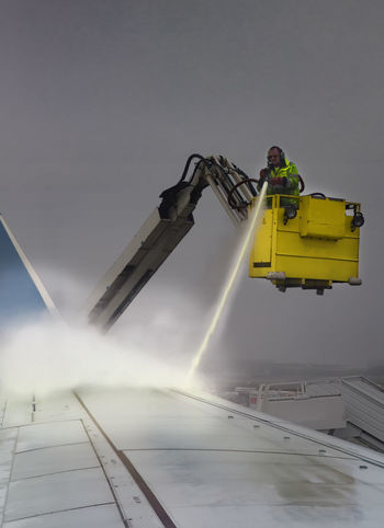 EyeEmNewHere Glycol And Water Glycol/ Water Spray Anti-icing Fluid Deicing Deicing Aircraft Deicing Airplane Air Vehicle Airplane Anti-icing Fluid Deicing Fluid Deicing The Wings Deicing/anti-icing Process Mode Of Transportation Nature Occupation Outdoors Real People Rescue Worker Sky Spray With High Pressure Spraying Transportation Wing Of Plane Yellow