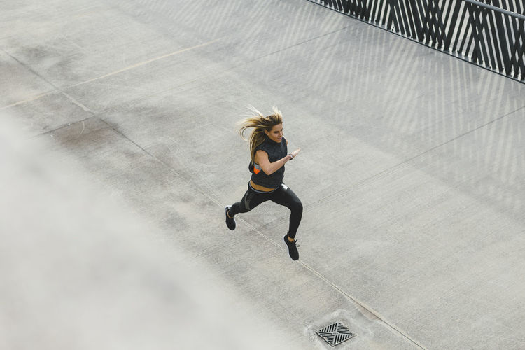 Woman running outdoors in the city, top view of fitness girl running Exercise Running Adult Day Effort Exercising Full Length Hair Hairstyle Healthy Lifestyle High Angle View Jogging Lifestyles Motion on the move One Person Outdoors Running Speed Sport Sports Sports Clothing Vitality Women Young Adult