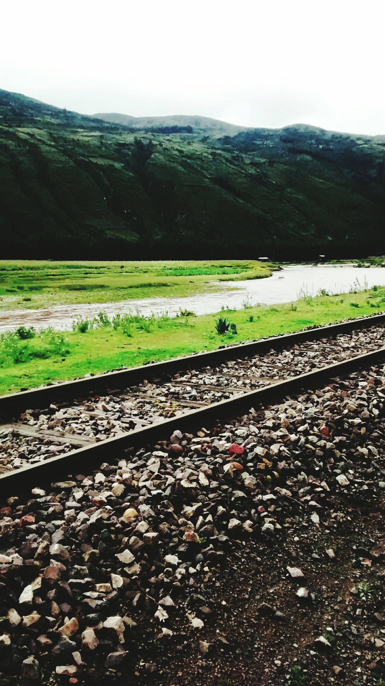 landscape, mountain, transportation, field, tranquil scene, tranquility, road, nature, clear sky, railroad track, scenics, rural scene, beauty in nature, sky, green color, rail transportation, agriculture, day, grass, outdoors