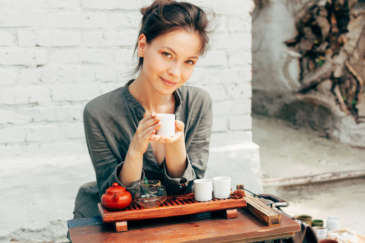 Beautiful woman preparing hot tea. Traditional tea ceremony. One Person Front View Cup Food And Drink Real People Mug Young Adult Day Drink Holding Portrait Women Lifestyles Adult Focus On Foreground Waist Up Casual Clothing Outdoors Drinking Contemplation Tea Ceremony Tea Tea - Hot Drink Tea Cup Woman