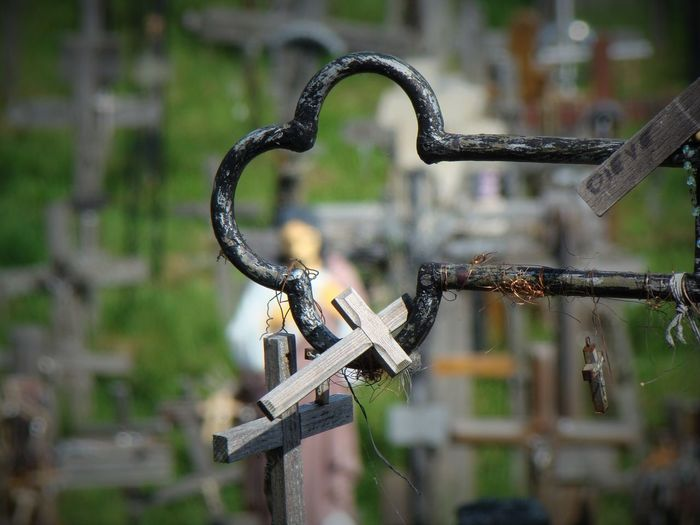 Close-Up Of Crosses Hanging On Metal In Cemetery
