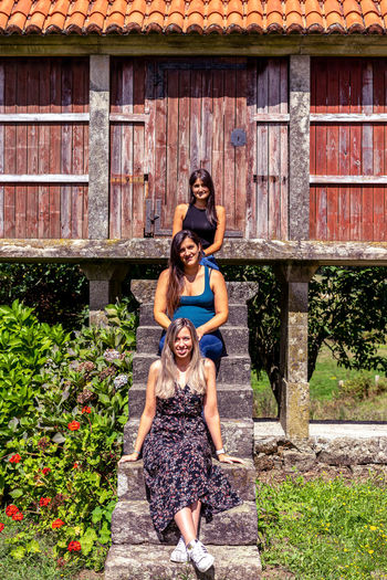 View of smiling women sitting on staircase against log cabin