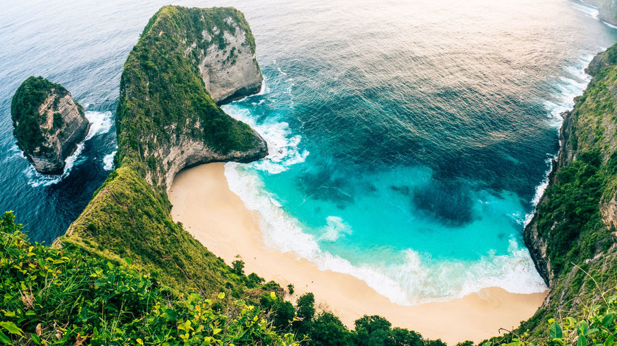 Aerial picture of a cliff with crystal blue water and gold beach in Indonesia. Bali landscape from top view from a mountain peak. Travel paradise destination for a couple in searching for adventure. Bali Blue Wave Drone  INDONESIA Nature Aerial View Amazing Beach Beauty In Nature Blue Cliff Day High Angle View Landscape Nature No People Outdoors Physical Geography Rock - Object Scenics Sea Sky Tranquility Tree Water