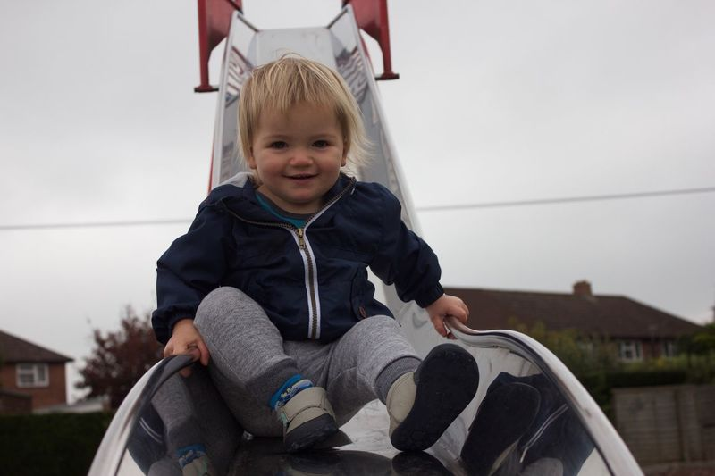 Portrait of smiling baby boy on slide at playground