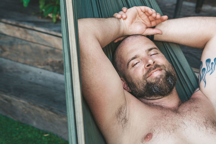 Relaxing in a hammock Lying Down Men Relaxation Headshot Beard Eyes Closed  One Person Shirtless Males  Portrait Young Adult Real People Leisure Activity Young Men Lifestyles Facial Hair Front View Lying On Back Mature Adult Mature Men Hands Behind Head Chest