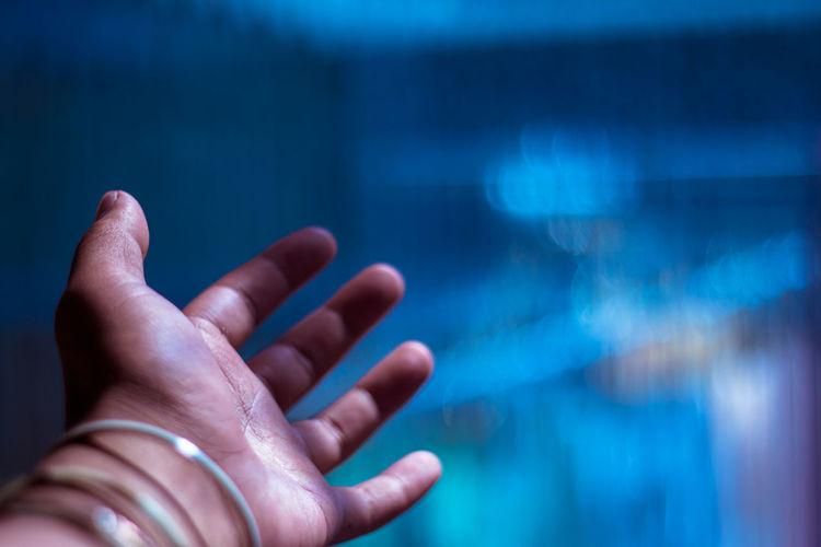 Close-up of hand gesturing illuminated light