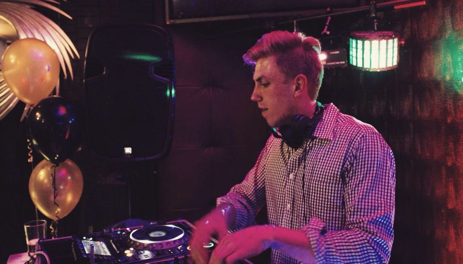 Young Male Dj Mixing Sound At Nightclub