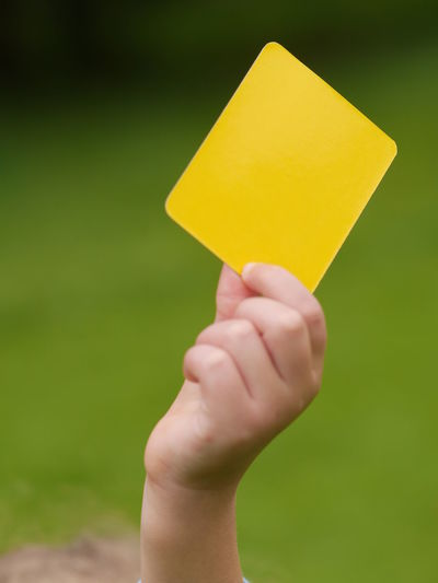 Cropped image of child holding yellow card during soccer match