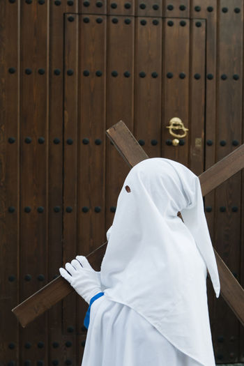 Side view of person wearing costume standing by wooden wall