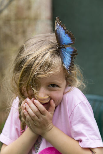 Portrait Of Smiling Girl With Butterfly In Hair Outdoors