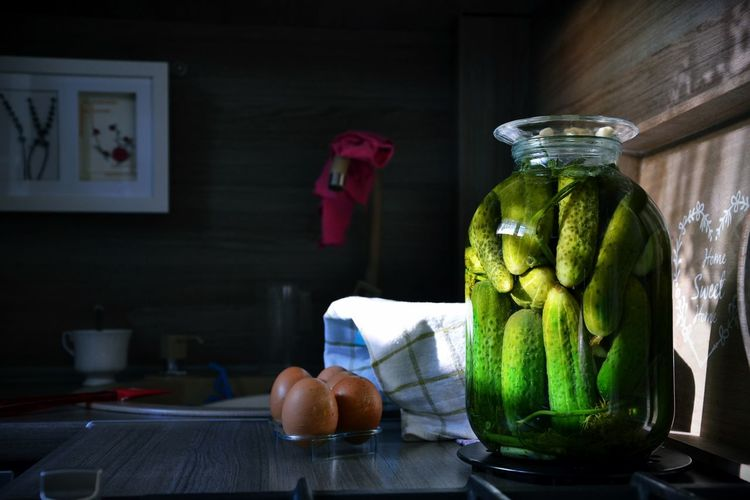 Close-up of cucumber pickle in jar by eggs on table at home