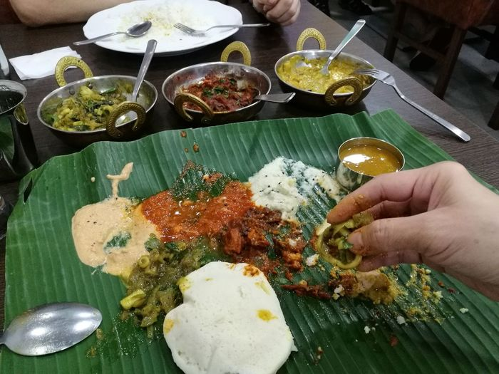 The best way of enjoying an Indian meal Human Hand Food Human Body Part Food And Drink Ready-to-eat Freshness Indoors  Plate Serving Size Table Meal Indian Meal Spicy Food Indian Cuisine Idlis And A Couple Of Chutneys Idlis Banana Leaf Meals Satisfying Asian Dish The Week On EyeEm Food Stories
