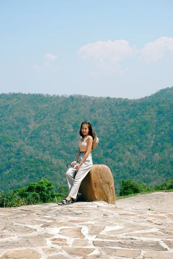 Full length of woman sitting on mountain against sky