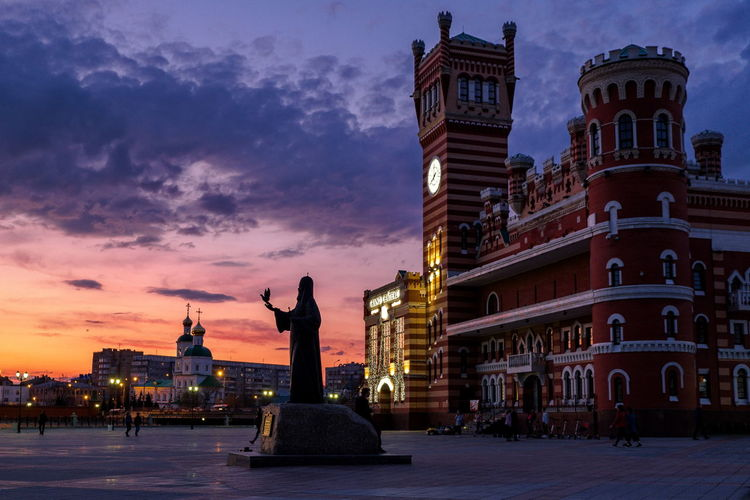 Statue of historic building against sky at sunset