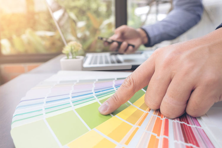 Cropped hand of businessman touching color swatch at table in office