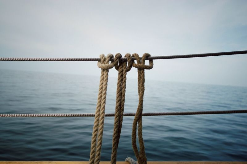 Close-Up Of Ropes Against Calm Sea