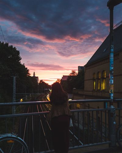 Rear view of silhouette woman standing by railing against sky