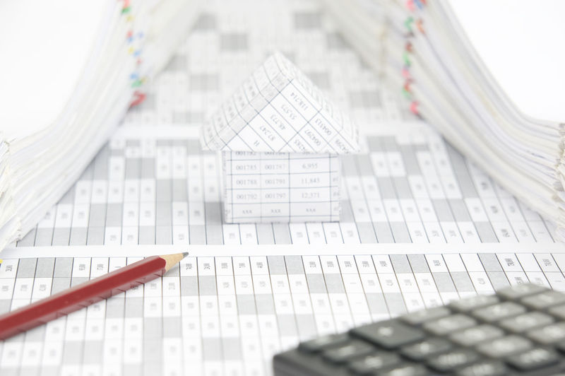 High angle view of model house with calculator and pencil on financial documents