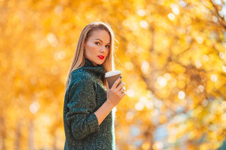 Portrait of beautiful young woman standing in park during autumn