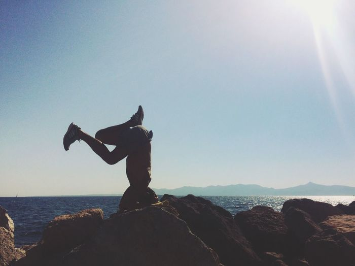 Man doing headstand on rock by sea against clear sky