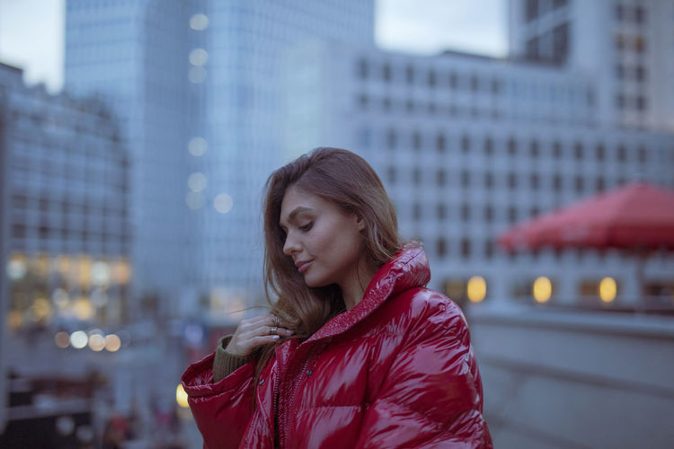 Close-Up Of Thoughtful Young Woman Wearing Warm Clothing In City During Sunset