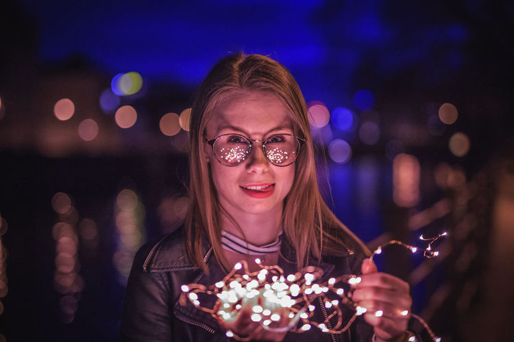 Portrait of young woman wearing eyeglasses holding illuminated string lights in city at night