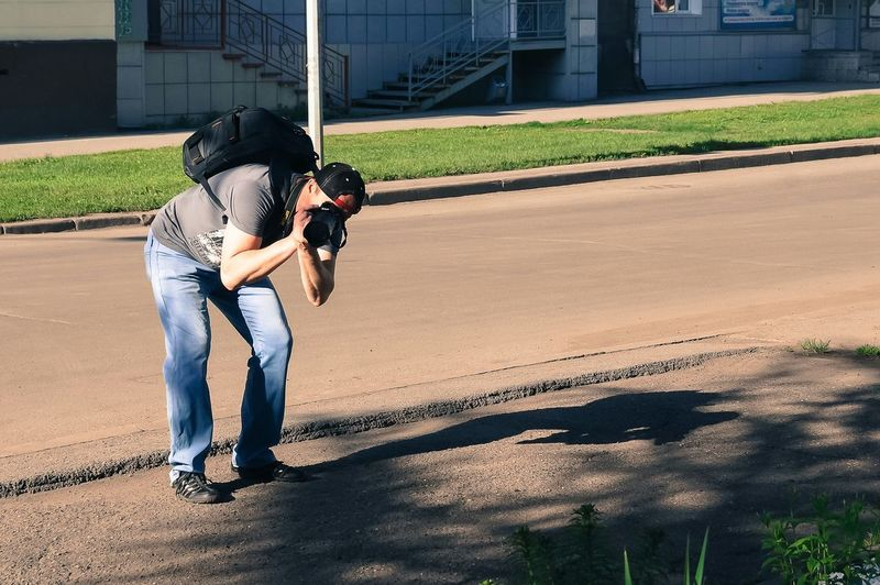 Man photographing while bending on street against building