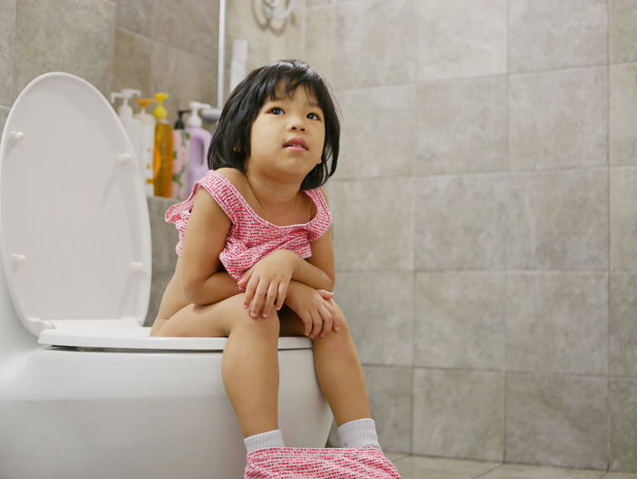 Little Asian baby girl, 38 months old, being happy to be able to get on and use adult size toilet bow by herself successfully Toilet Bowl Toilet Baby Girl Asian  Toddler  Young Litle Kid Child Female Training Potty At Home Successfully By Herself Sitting Pee Poo Poop Happy Adult-size Learning Skill  Routine Habit