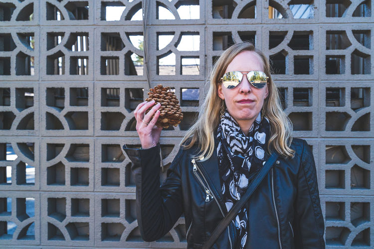 Attractive blonde haired woman holds up large pinecone to her head against geometric lattice person