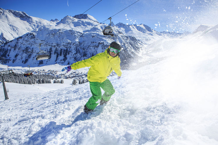 Young Man Skiing On Snowcapped Mountains During Winter