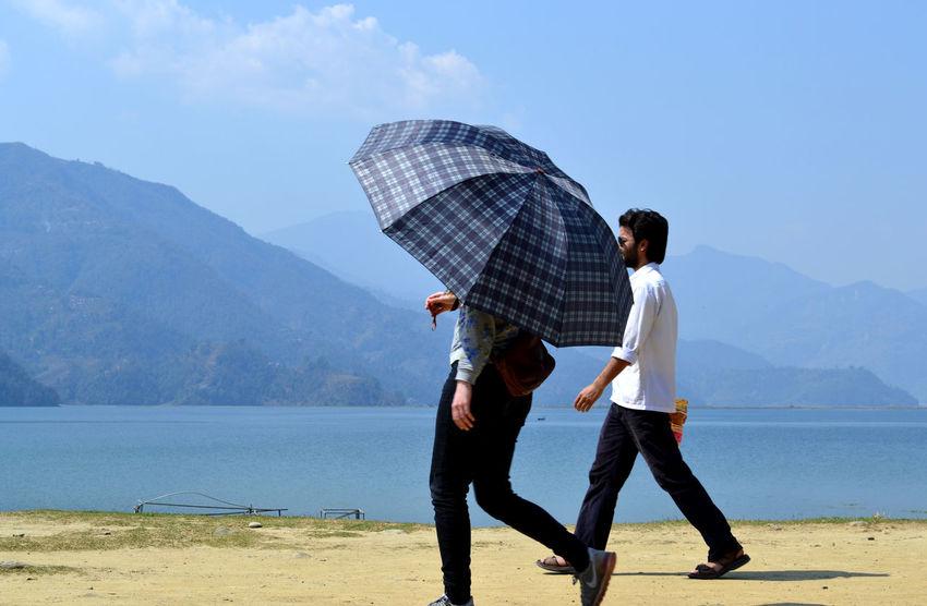 walking by the Phewa Lake Two People Big Umbrella Pokhara, Nepal