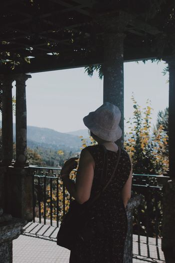 Rear view of woman wearing hat standing in old built structure