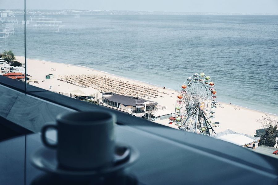 Glass Beach Beach Umbrellas Coffee Coffee Cup Focus On Background Water Sea High Angle View Close-up Coffee - Drink The Great Outdoors - 2018 EyeEm Awards