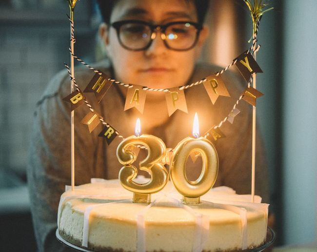 Close-up of woman looking at burning 30 number candle on birthday