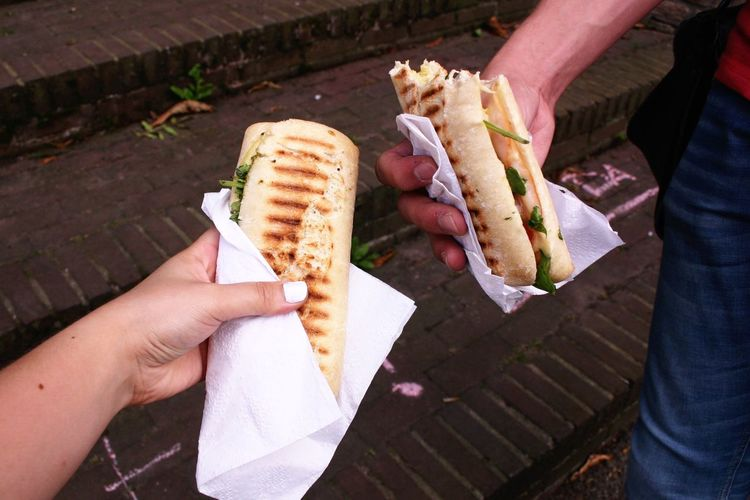 Cropped image of friends holding panini on steps