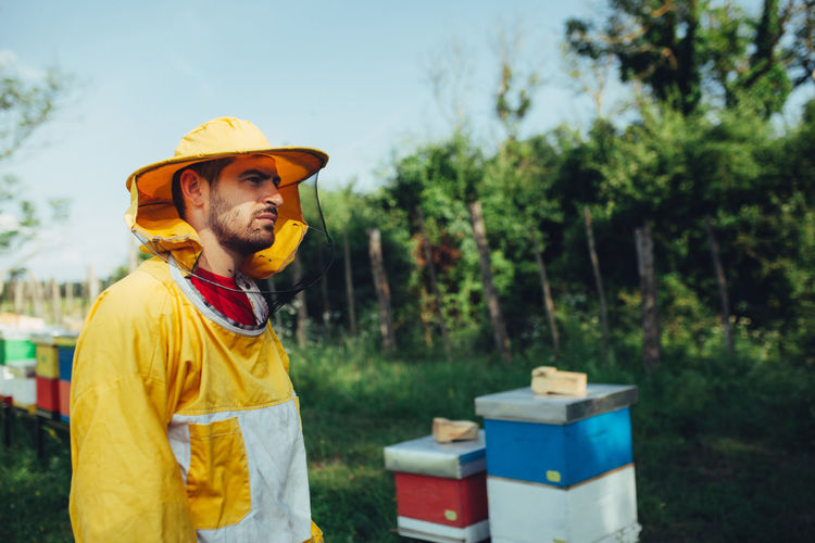 Side view of beekeeper standing by beehives on land