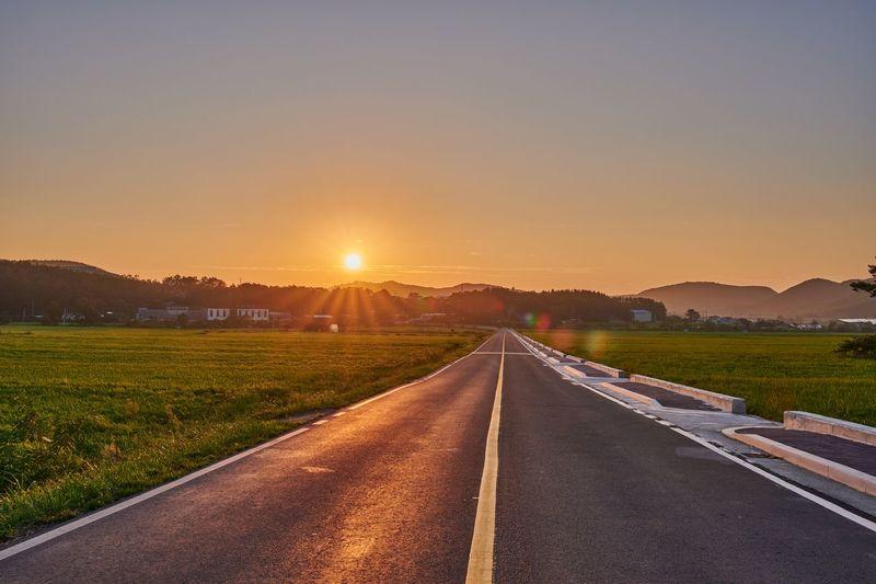 Empty road along landscape at sunset