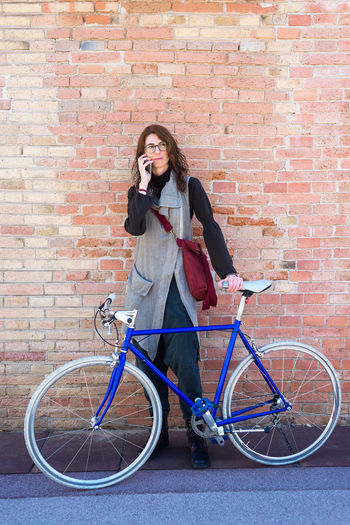 Woman with bicycle standing against brick wall