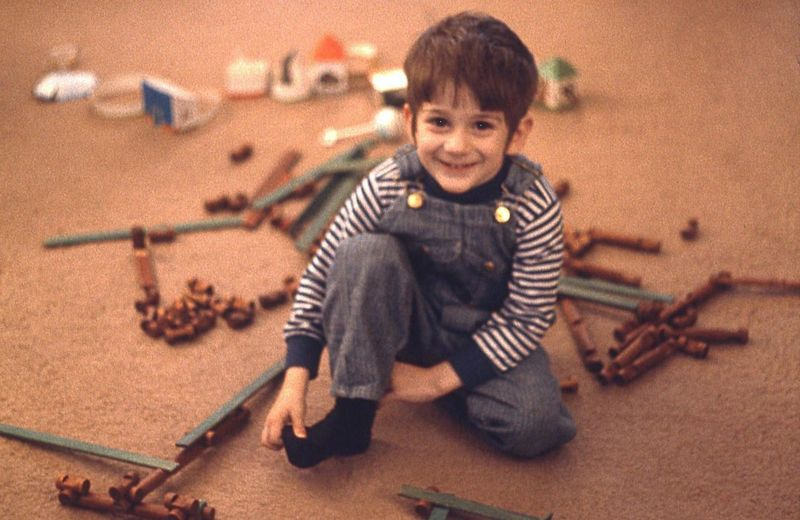 High angle portrait of boy playing with wooden toys on carpet