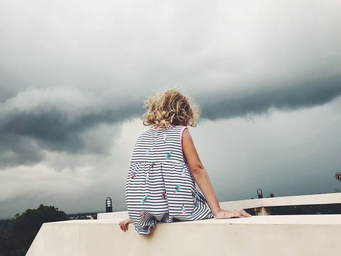 Rear View Of Girl Sitting On Wall Against Cloudy Sky