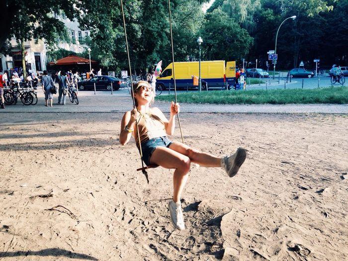 Full length of a cute girl sitting on swing