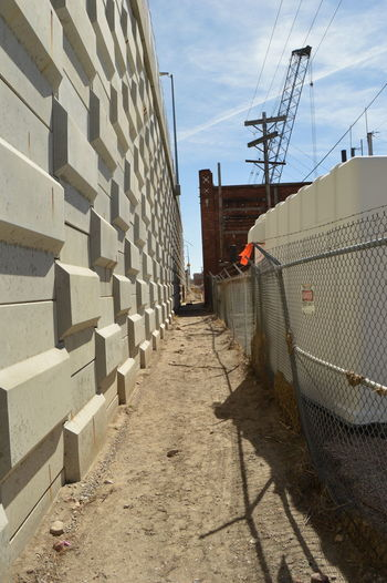 Narrow Walkway By Wall And Fence At Construction Site