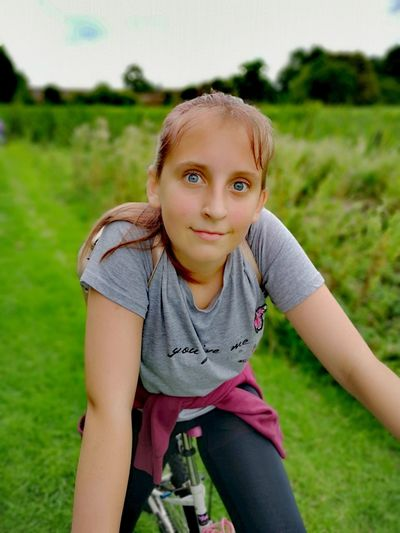 Portrait of girl riding bicycle on field