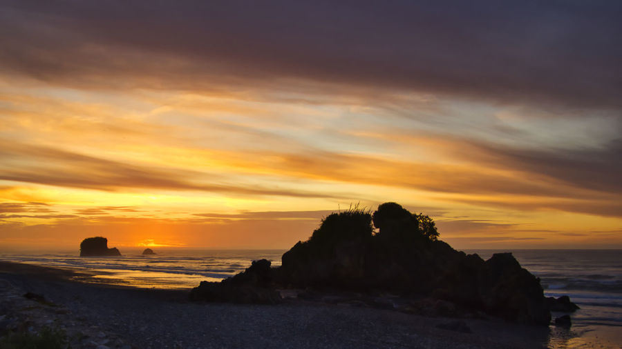 Sunset at Torea Rocks, Granity, New Zealand Torea Rocks South Island NZ New Zealand Landscape Stack Rock Outdoors No People Horizon Idyllic Nature Horizon Over Water Solid Orange Color Rock - Object Tranquil Scene Land Rock Cloud - Sky Beach Scenics - Nature Beauty In Nature Water Sea Sky Sunset Silhouette