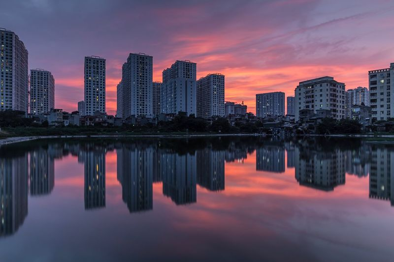 Reflection of buildings in river at sunset